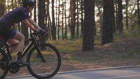 De vrouwelijke fiets van de fietser berijdende weg in het park met de zon die door bomen glanzen Cinematic het cirkelen concept stock video