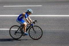 De vrouwelijke fietser berijdt een het rennen fiets op weg Royalty-vrije Stock Fotografie