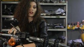De vrouwelijke fietser leunt op de motorfietstank stock video