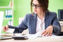 De vrouwelijke financiële manager die in het bureau werken stock foto's