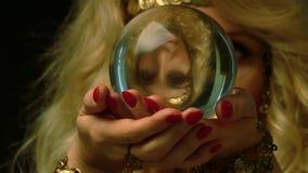 De vrouwelijke fortuinteller kijkt binnen aan de toekomst door kristallen bol stock videobeelden