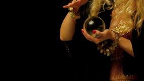 De vrouwelijke fortuinteller kijkt binnen aan de toekomst door kristallen bol stock footage