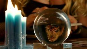 De vrouwelijke fortuinteller kijkt binnen aan de toekomst door kristallen bol stock video