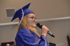 De vrouwelijke gediplomeerde geeft een toespraak bij haar graduatie stock foto