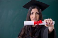 De vrouwelijke gediplomeerde student voor groene raad stock fotografie