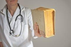 Vrouwelijke geneeskundestudent die een boek houden Stock Foto's