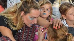 De vrouwelijke grimeur schildert het gezicht van een jong meisje (Zandvoort, Noord-Holland, Nederland - ca Oktober 2015) Stock Foto's