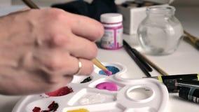 De vrouwelijke hand dompelt de borstel in roze verf in palet onder, dan mengt het met wit stock videobeelden