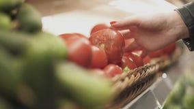 De vrouwelijke hand draagt een plank met tomaten en neemt lelijke tomaat in zijn hand stock video