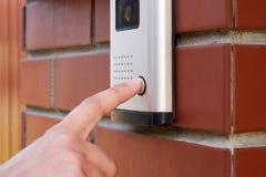 De vrouwelijke hand drukt een knoopdeurbel met intercom royalty-vrije stock foto's