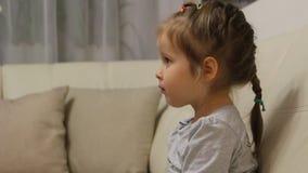 De vrouwelijke hand geeft een appel aan een kind Het kind die groene appel eten die op TV letten stock video