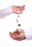 De vrouwelijke hand giet onderaan muntstukken in mannelijke handen Stock Afbeeldingen
