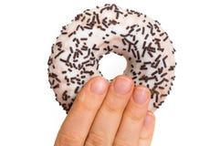 De vrouwelijke hand houdt de doughnut met bestrooit stock afbeelding