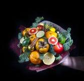 De vrouwelijke hand houdt een unie van fruit, op een zwarte achtergrond Vierkante foto stock fotografie