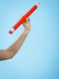 De vrouwelijke hand houdt groot rood potlood royalty-vrije stock afbeeldingen