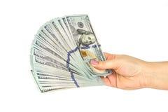 De vrouwelijke hand houdt heel wat dollarsbankbiljetten op een witte achtergrond Sluit omhoog Stock Foto's