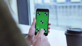 De vrouwelijke hand houdt het apparaat met het groene scherm, drinkt koffie, en glijdt omhoog het scherm Voorbijgangers op de ach stock video