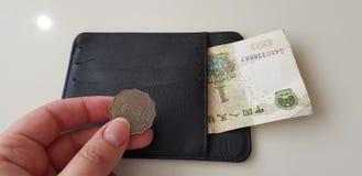 De vrouwelijke hand houdt twee dollarsmuntstuk van Hongkong stock afbeeldingen