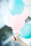 De vrouwelijke hand houdt vliegende ballons Stock Foto's