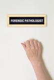 De vrouwelijke hand klopt op Gerechtelijke Patholoogdeur Stock Fotografie