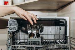 De vrouwelijke hand legt de schotels in een open afwasmachineclose-up dat met schone, gewassen schotels wordt belemmerd droge bes stock afbeeldingen
