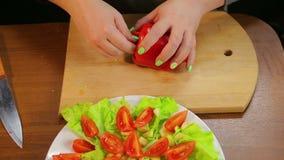 De vrouwelijke hand maakt peper van de kern met een mes schoon stock videobeelden
