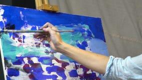 De vrouwelijke hand met borstel maakt tot vlekken zwarte verf op canvas stock videobeelden