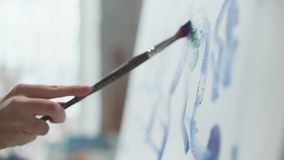 De vrouwelijke hand met een borstel trekt op een canvas, close-up stock video