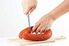 De vrouwelijke hand met een mes sneed gerookte worst Royalty-vrije Stock Afbeeldingen