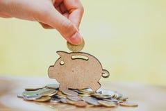 De vrouwelijke hand muntstuk zetten en de stapel die muntstukken in concept besparingen en geld het groeien of energie sparen stock afbeeldingen