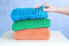 De vrouwelijke hand neemt badstofhanddoeken op een witte bedlijst in de badkamers royalty-vrije stock fotografie