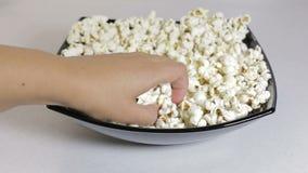 De vrouwelijke hand neemt de popcorn van een plaat stock video