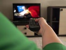 De vrouwelijke hand neemt het verre, achterstandpunt van TV in royalty-vrije stock foto