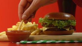 De vrouwelijke hand onderdompelende frieten in tomatensaus, snel voedselrestaurant, sluiten omhoog stock videobeelden