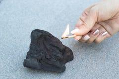 De vrouwelijke hand plaatst brand aan steenkool, close-up royalty-vrije stock fotografie