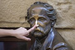 De vrouwelijke hand raakt de neus van het bronsbeeldhouwwerk in de straatkoffie, Lviv, de Oekraïne Sluit omhoog stock afbeeldingen
