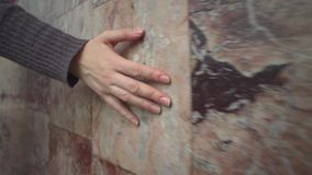 De vrouwelijke hand raakt de roze marmeren muur stock videobeelden