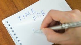 De vrouwelijke hand schrijft een motieveninschrijving op papier Tijd voor actie stock video