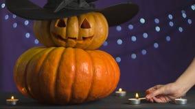 De vrouwelijke hand steekt een kaars naast de pompoenen voor Halloween aan royalty-vrije stock afbeeldingen
