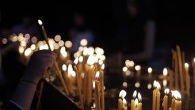 De vrouwelijke hand steekt kaarsen van kaarsvlam aan en zette het dichtbij andere kaarsen stock footage