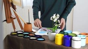 De vrouwelijke hand van de kunstenaar, mengt de kleuren op de Raad, en treft voorbereidingen om een beeld met acrylverven te schi stock footage