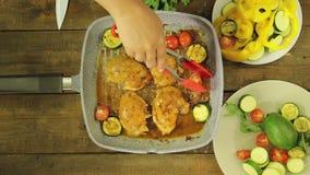De vrouwelijke hand zet groenten in kippenstukken in een grillpan stock video