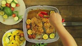 De vrouwelijke hand zet groenten in kippenstukken in een grillpan stock footage