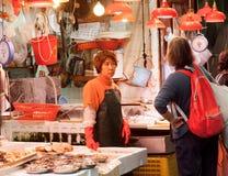 De vrouwelijke handelaren van vissenmarkt spreiden zeevruchten voor verkoop op een straatdienblad uit Royalty-vrije Stock Foto's