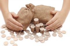 De vrouwelijke handen beschermt zakken met geld royalty-vrije stock afbeelding