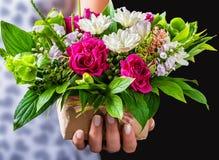 De vrouwelijke handen die gift en uitstekend huwelijksboeket houden van namen toe Royalty-vrije Stock Foto