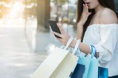 De vrouwelijke handen die het winkelen houden doet in zakken Stock Afbeeldingen
