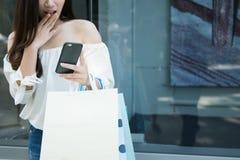 De vrouwelijke handen die het winkelen houden doet in zakken en kijken een smartphoneschok Stock Foto's