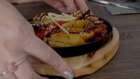 De vrouwelijke handen dienen pan met groenten onder sesam op houten dienblad stock footage