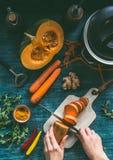 De vrouwelijke handen gezonde soep koken of de groenten die stoven met oranje kleuren vegetarische ingrediënten: pompoen, wortele stock afbeelding